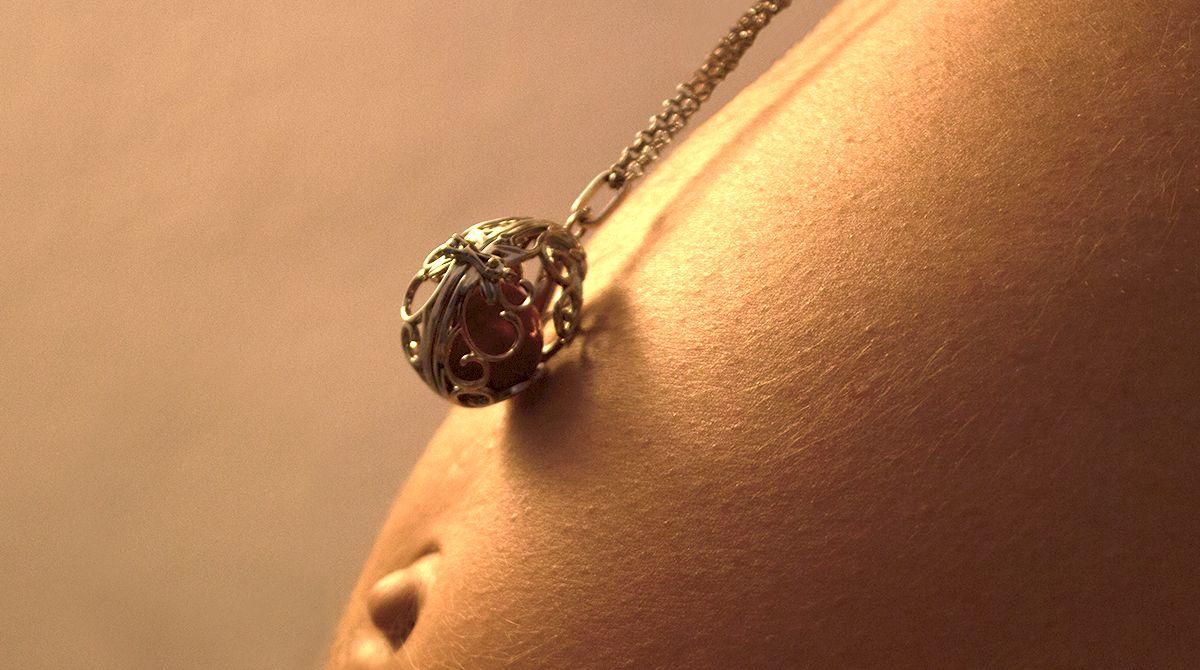 Bola de grossesse couleur or avec pierre rouge sur ventre de femme enceinte